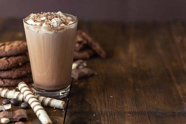 Tasse kakao mit marshmallows und schokoladenplätzchen auf dunklem hölzernem hintergrund