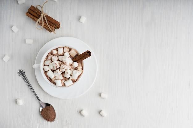 Tasse kakao mit marshmallows, zimtbündel und löffel auf weißem hölzernem hintergrund.