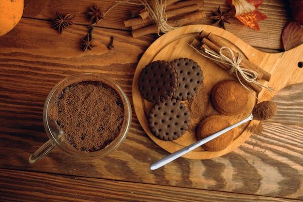 Tasse kakao-schokoladenkekse und zimtstangen auf holztisch-herbstkomposition für postkarten ...