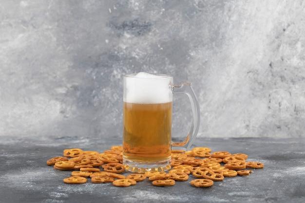 Tasse kaltes schaumiges bier und gesalzene brezeln auf marmoroberfläche.