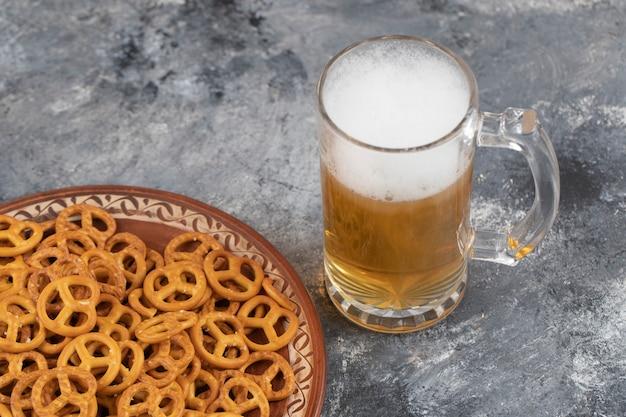 Tasse kaltes schaumiges bier und gesalzene brezeln auf marmoroberfläche
