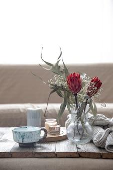 Tasse, kerzen, vase mit protea-blumen und ein gestricktes element im raum auf unscharfem hintergrund.