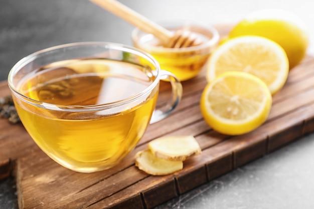 Tasse köstlichen tee mit zitrone und ingwer auf holzbrett