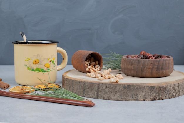 Tasse kräutertee, getrocknete preiselbeeren und süßigkeiten auf marmortisch. hochwertiges foto