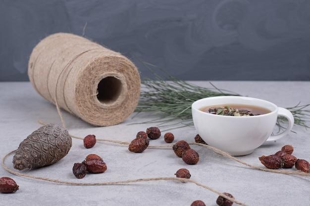 Tasse kräutertee, getrocknete preiselbeeren und tannenzapfen auf marmortisch.