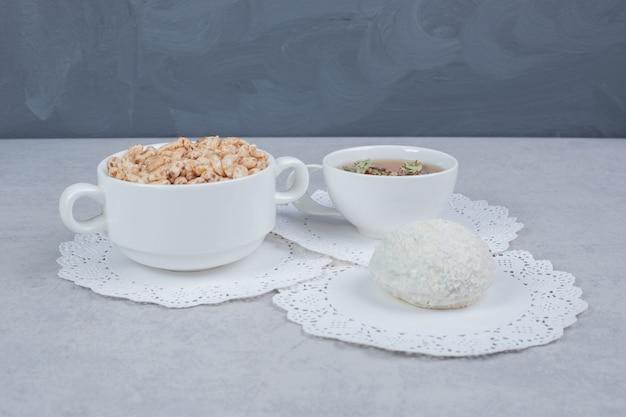 Tasse kräutertee, kokosnusskeks und schüssel mit süßigkeiten auf weißem tisch.