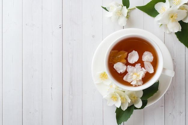 Tasse kräutertee mit blütenblättern von jasminblüten