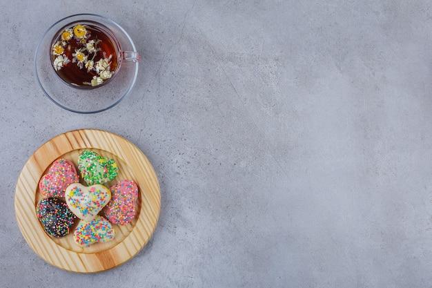 Tasse kräutertee mit teller mit süßen keksen auf stein.