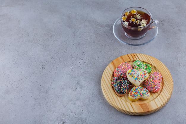 Tasse kräutertee mit teller mit süßen keksen auf steinhintergrund.