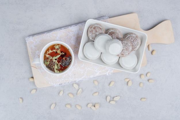 Tasse kräutertee und teller mit verschiedenen keksen auf holzbrett. hochwertiges foto