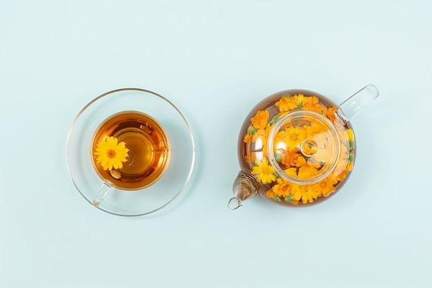 Tasse kräutertee und transparente teekanne mit ringelblumenblumen auf blauem hintergrund. calendula tea kommt ihrem gesundheitskonzept zugute.