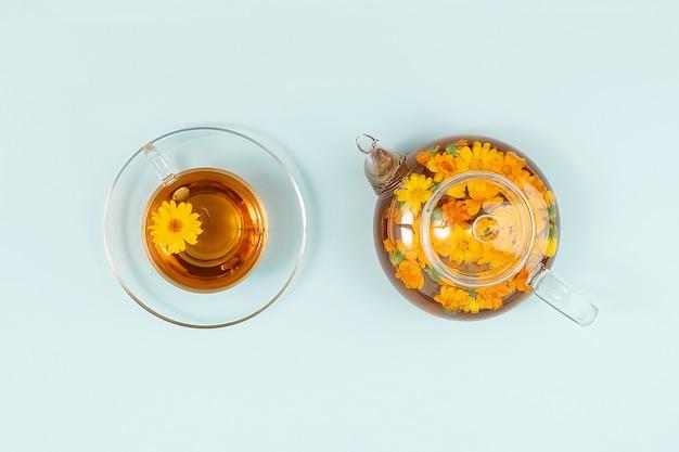 Tasse kräutertee und transparente teekanne mit ringelblumenblumen auf blauem hintergrund. calendula tea kommt ihrem gesundheitskonzept zugute