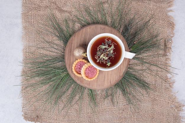 Tasse kräutertee, weihnachtskugel und kekse auf holzteller. hochwertiges foto