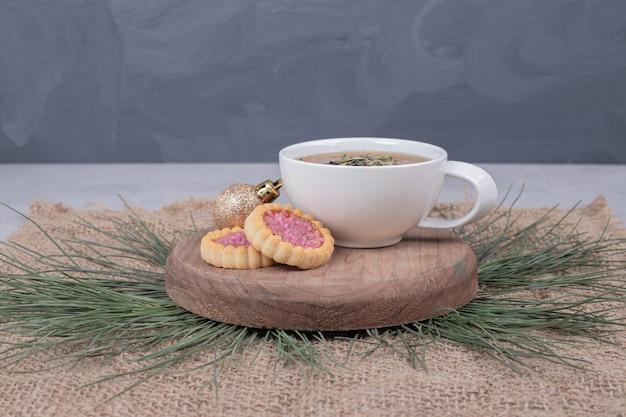 Tasse kräutertee, weihnachtskugel und kekse auf holzteller.