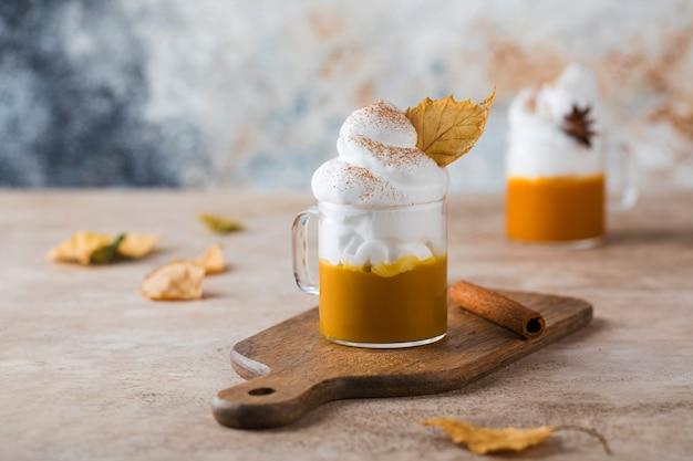 Tasse kürbiskaffee mit schlagsahne und trockenem blatt