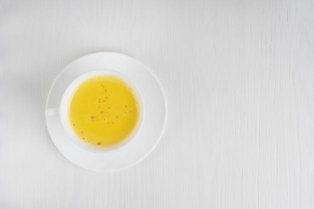 Tasse kurkuma milch auf teller auf weißem holztisch serviert