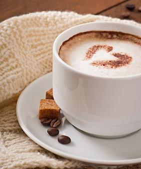 Tasse latte auf dem alten hölzernen hintergrund