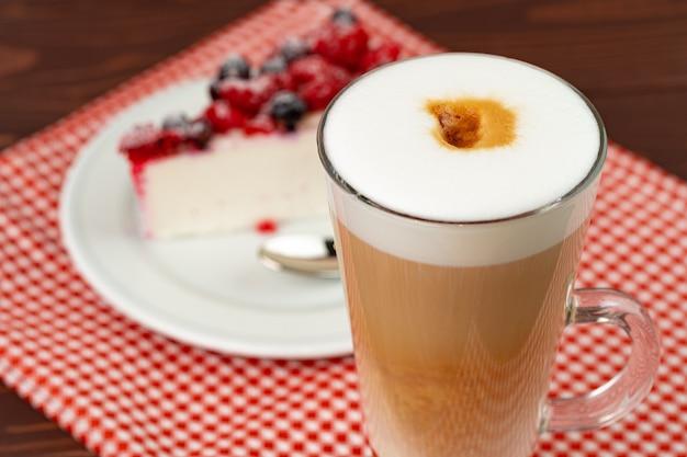 Tasse latte kaffee mit stück beerenkäsekuchen