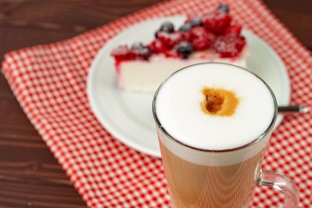 Tasse lattekaffee mit einem stück beerenkäsekuchen