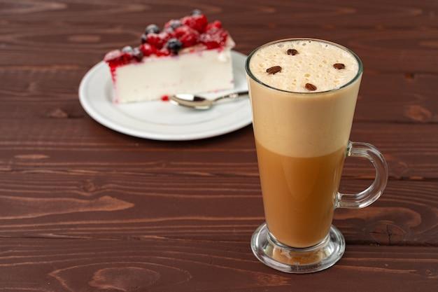 Tasse lattekaffee mit stück beerenkäsekuchen hautnah