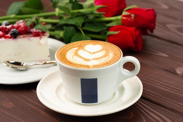 Tasse lattekaffee mit stück beerenkäsekuchen nah oben