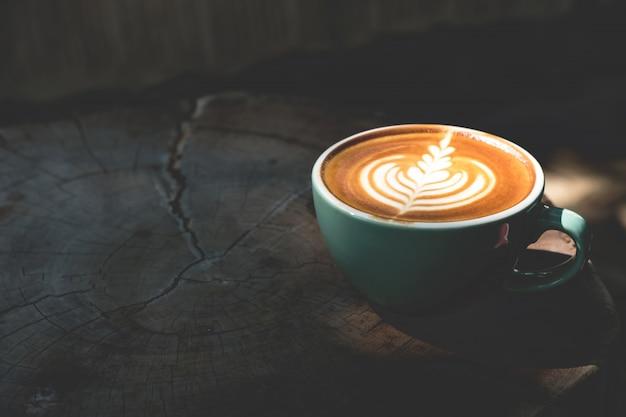 Tasse lattekaffee steht auf holztisch mit schatten- und sonnenlicht.