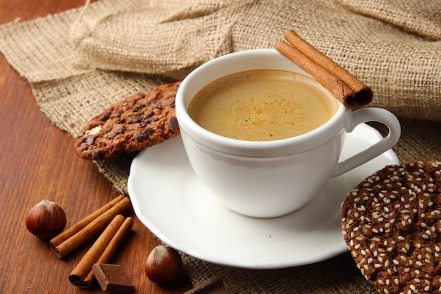 Tasse leckeren kaffees mit leckeren keksen auf holztisch