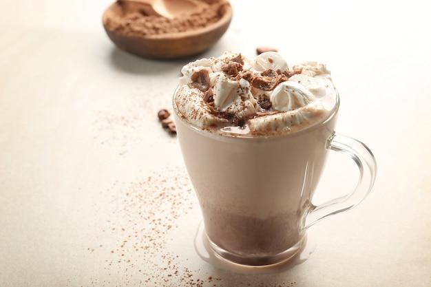 Tasse leckeres kakaogetränk mit marshmallow auf hellem hintergrund