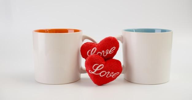Tasse liebe, zwei kaffeetassen mit roter herzikone auf weißem hintergrund