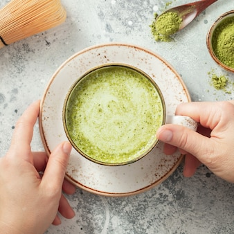 Tasse matcha-grüntee in frauenhänden.