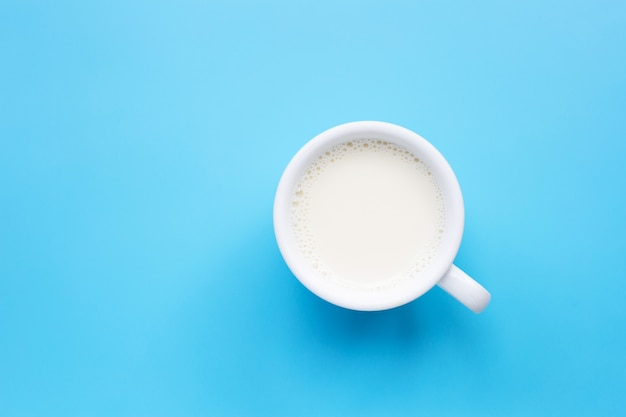 Tasse milch auf blauem hintergrund.