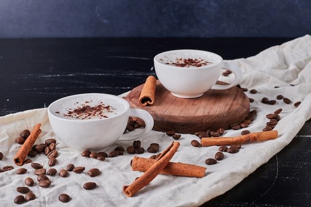 Tasse milch mit kaffeepulver und bohnen.