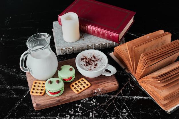 Tasse milch mit kaffeepulver und macarons.