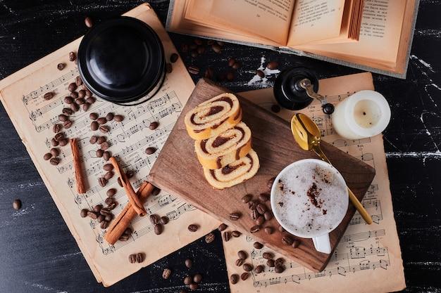 Tasse milch mit kaffeepulver und rollcake.
