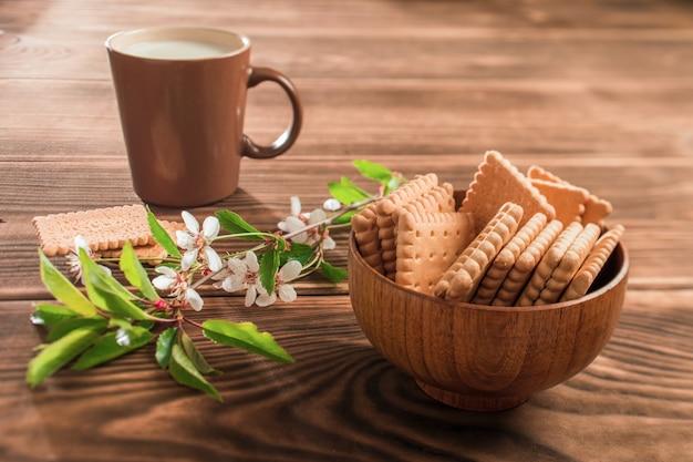 Tasse milch und kekse auf dem teller auf dem tisch