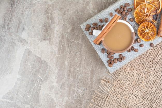 Tasse milchkaffee mit kaffeebohnen und orangenscheiben auf buch.