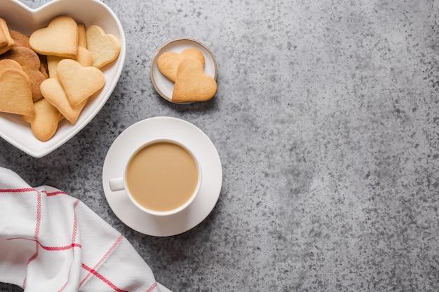 Tasse milchkaffee und handgemachte kekse in form des herzens auf grauem steinhintergrund. valentinstagskarte. flache lage, draufsicht, kopierraum.