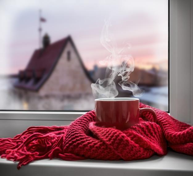 Tasse mit einem heißen getränk auf der fensterbank