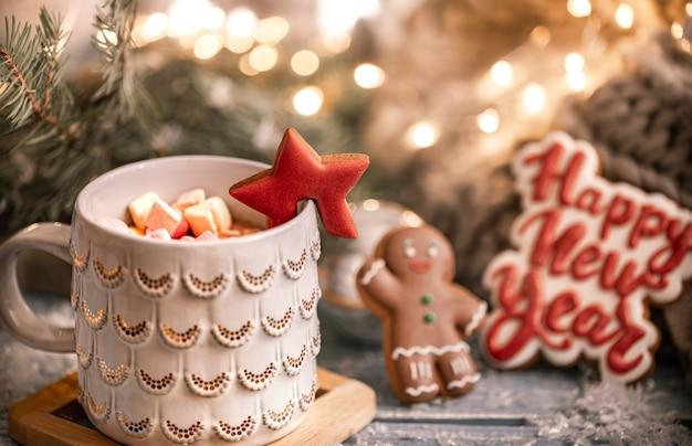 Tasse mit einem heißen getränk, marshmallow auf einem tisch mit weihnachtsdekorationen auf hintergrund mit lebkuchenplätzchen. neujahrskonzept.