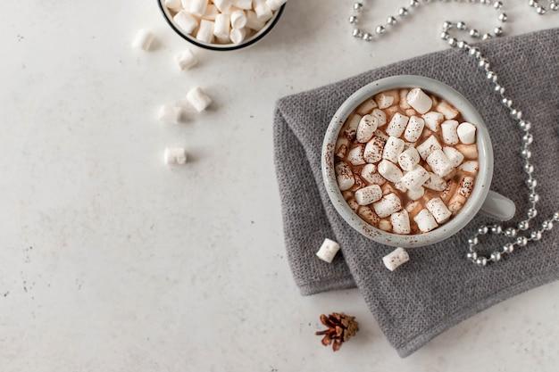 Tasse mit einem heißen getränk und mini marshmallows in einer festlichen atmosphäre. weiß mit copyspace