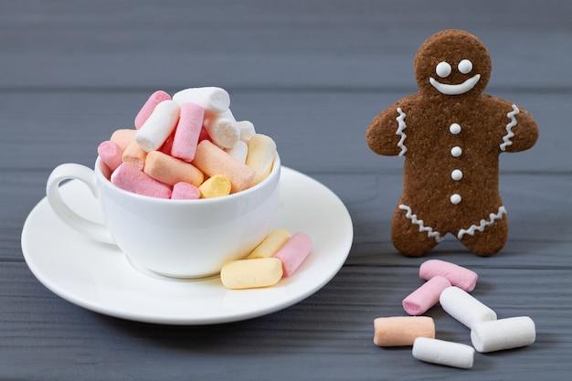 Tasse mit farbigem marshmellow und lächelndem lebkuchenmann-nahaufnahme auf hölzernem grauem hintergrund. weihnachtsbonbonkonzept