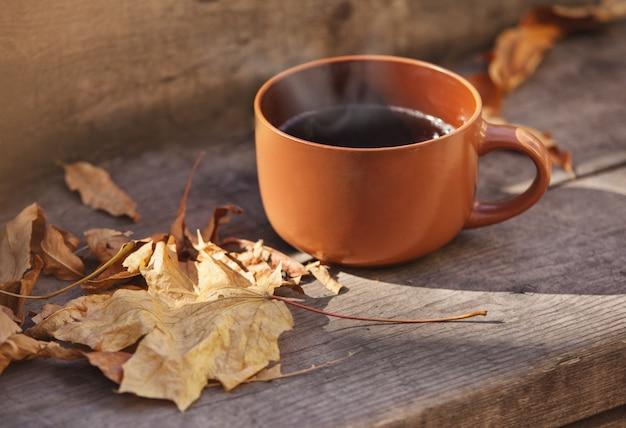 Tasse mit heißem getränk und blätter auf der treppe