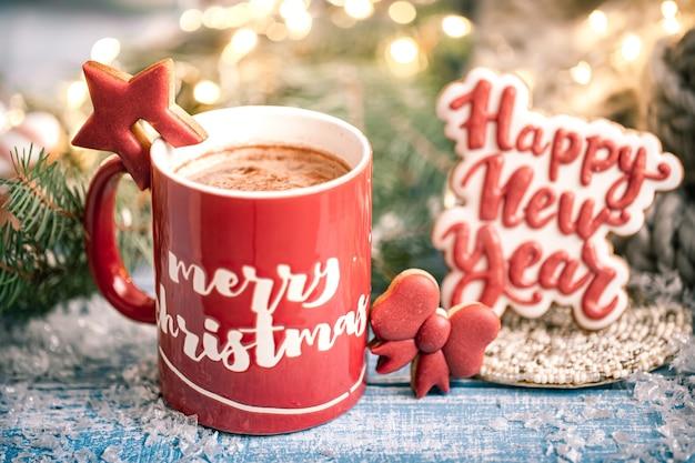 Tasse mit heißem getränk und lebkuchenplätzchen schließen. das neue jahr und winter zu hause komfort.