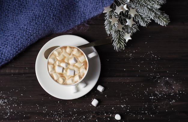 Tasse mit heißem getränk und marshmallows, gestrickte decke auf dunklem hölzernem hintergrund mit schnee