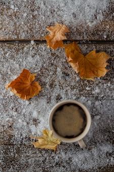 Tasse mit heißem kaffee, der auf schnee mit gelben blättern steht. outdoor-lifestyle-konzept. entspannen sie sich und ruhen sie sich aus. nahansicht.