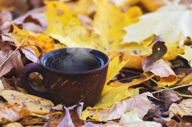 Tasse mit heißem kaffee oder tee im wald auf einem herbstgelben blatt