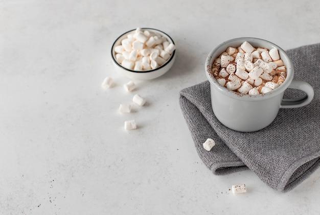 Tasse mit heißer schokolade und minieibischen mit einer gemütlichen decke auf einem weiß. flach liegen. ansicht von oben. copyspace