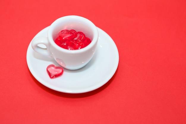 Tasse mit herzen auf rotem grund. der blick von oben. rote herzen ergossen sich. isoliert auf einem rosa hintergrund. speicherplatz kopieren