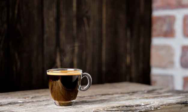 Tasse mit kaffee-espresso auf einem dunklen holztisch angeordnet. nahaufnahme, selektiver fokus, kopierraum