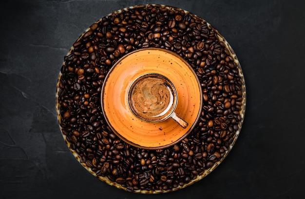 Tasse mit kaffee-espresso auf einem dunklen tisch angeordnet. geröstete kaffeebohnen befinden sich um eine tasse kaffee. draufsicht